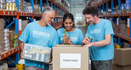 Three volunteers packing eatables in cardboard box