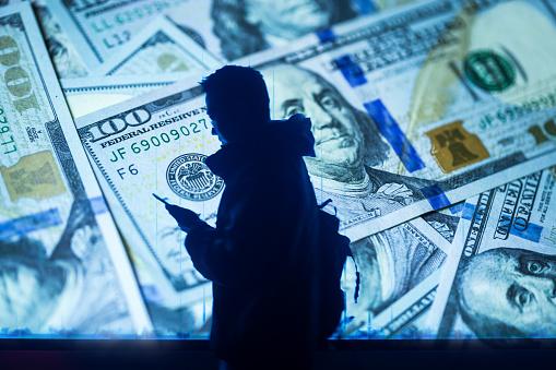 man walking through screen with 100 dollar money